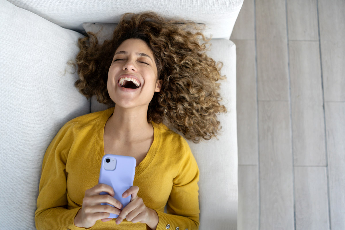 A woman lays down on her couch with her phone in her hand. Her expression on her face is excitement and happiness.