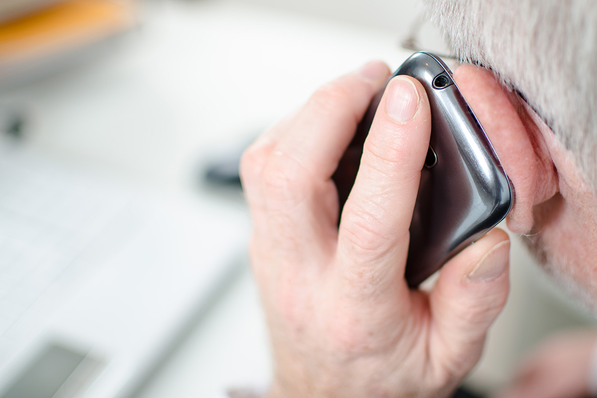 A middle-aged man holds a phone up to his ear as he speaks to someone.