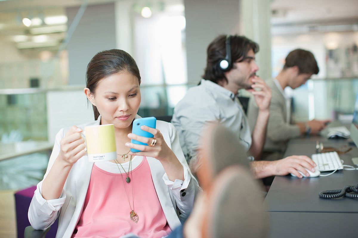 Businesswoman drinking coffee and looking at phone with feet up in office
