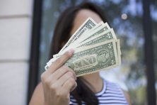 girl holding money in front of face