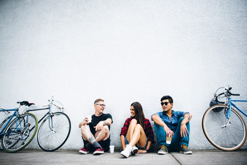 A trio of friends sit on the sidewalk sipping coffee while taking a break from bike riding.