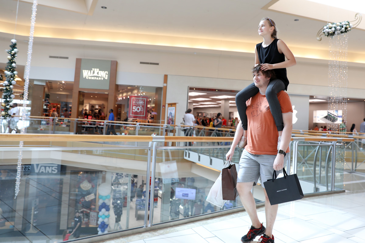 A Gen Z sits on her brother's shoulders while shopping at the mall.