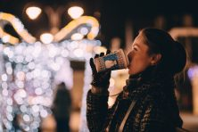 a women drinking coffee outside with christmas lights in the background