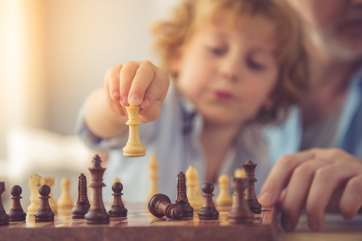 Kid playing one of the most popular board games of all time: chess