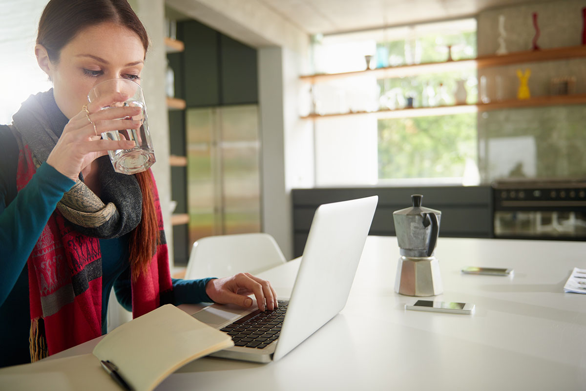Cropped shot of an attractive young woman drinking water while using a laptop with an open journal on the side