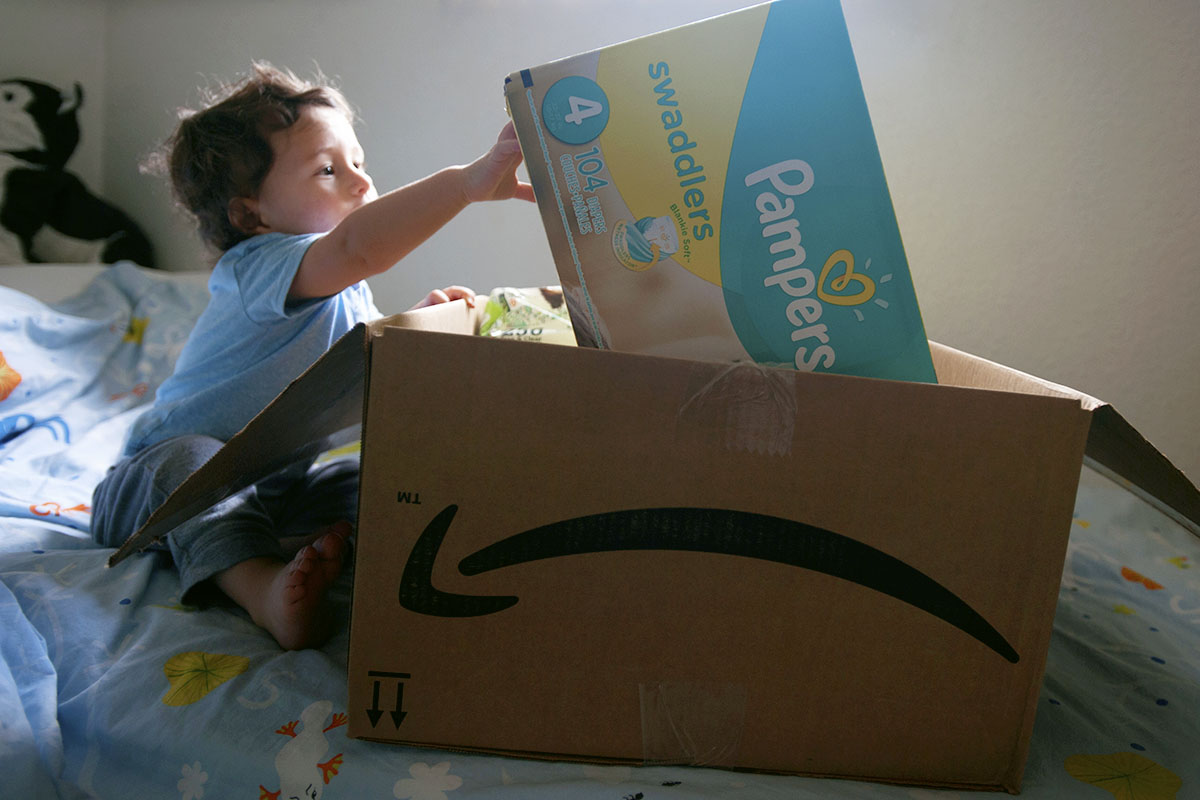 Ezra Avila, 1, reaches for a box of diapers in an Amazon box on August 11, 2017 in St. Petersburg, Fla