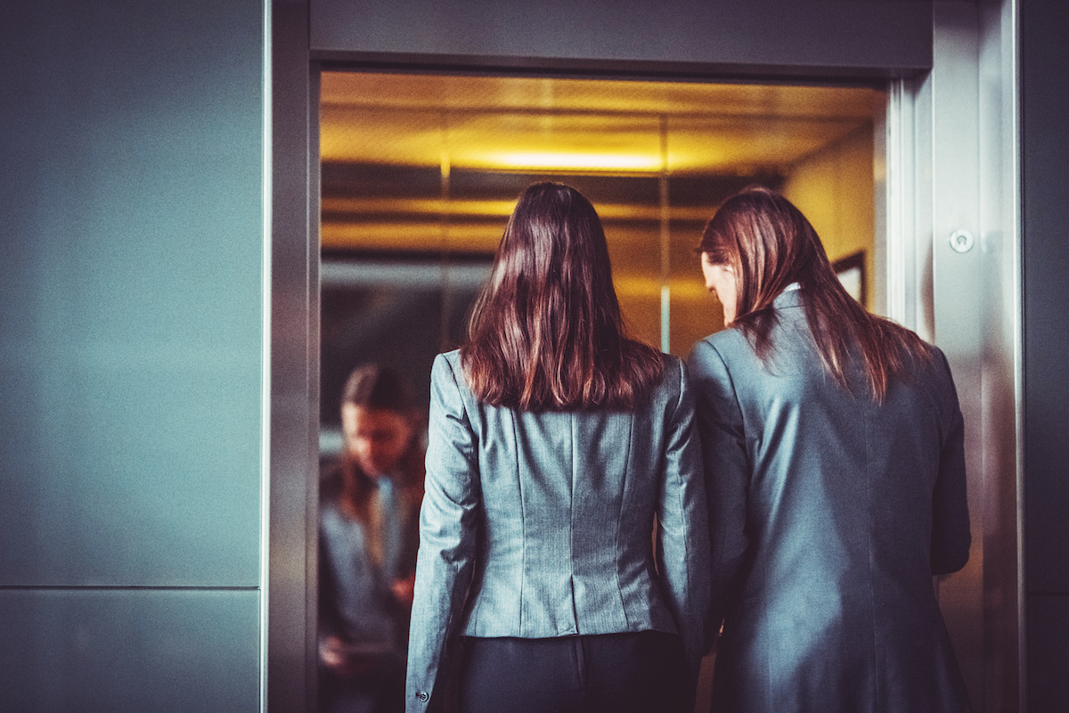 2 women stepping into an elevator