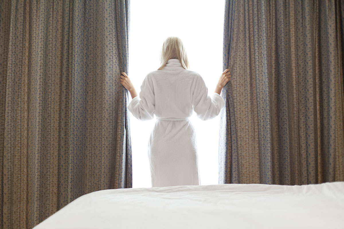 woman looking out window in hotel room