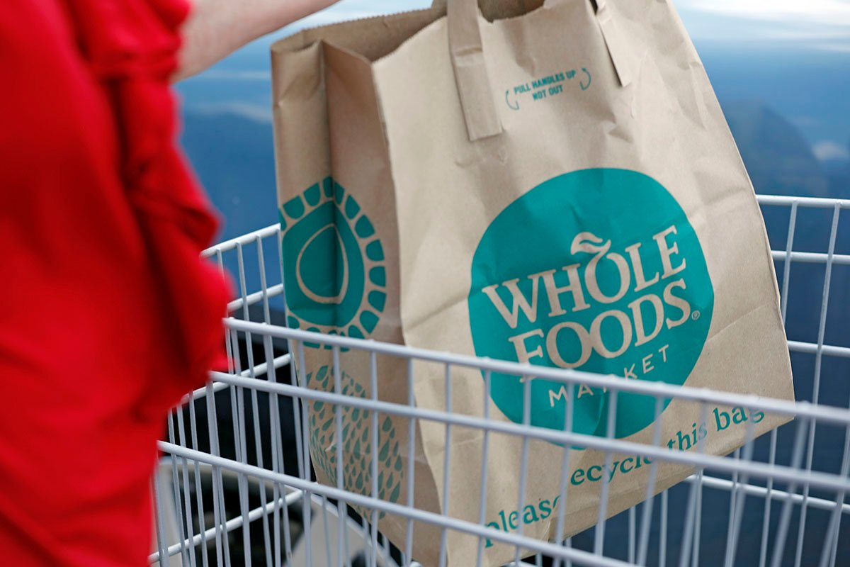 A Whole Foods Market customer carries her purchase
