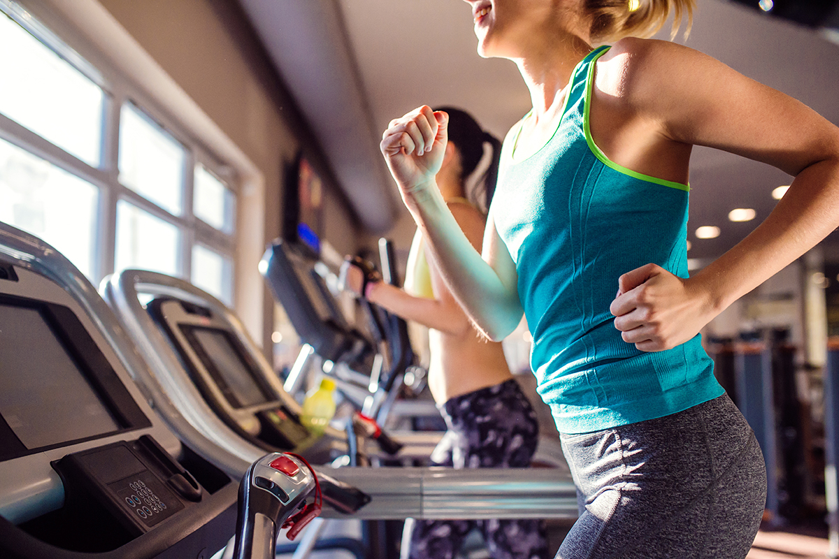 women running in sports clothes on treadmills in modern gym
