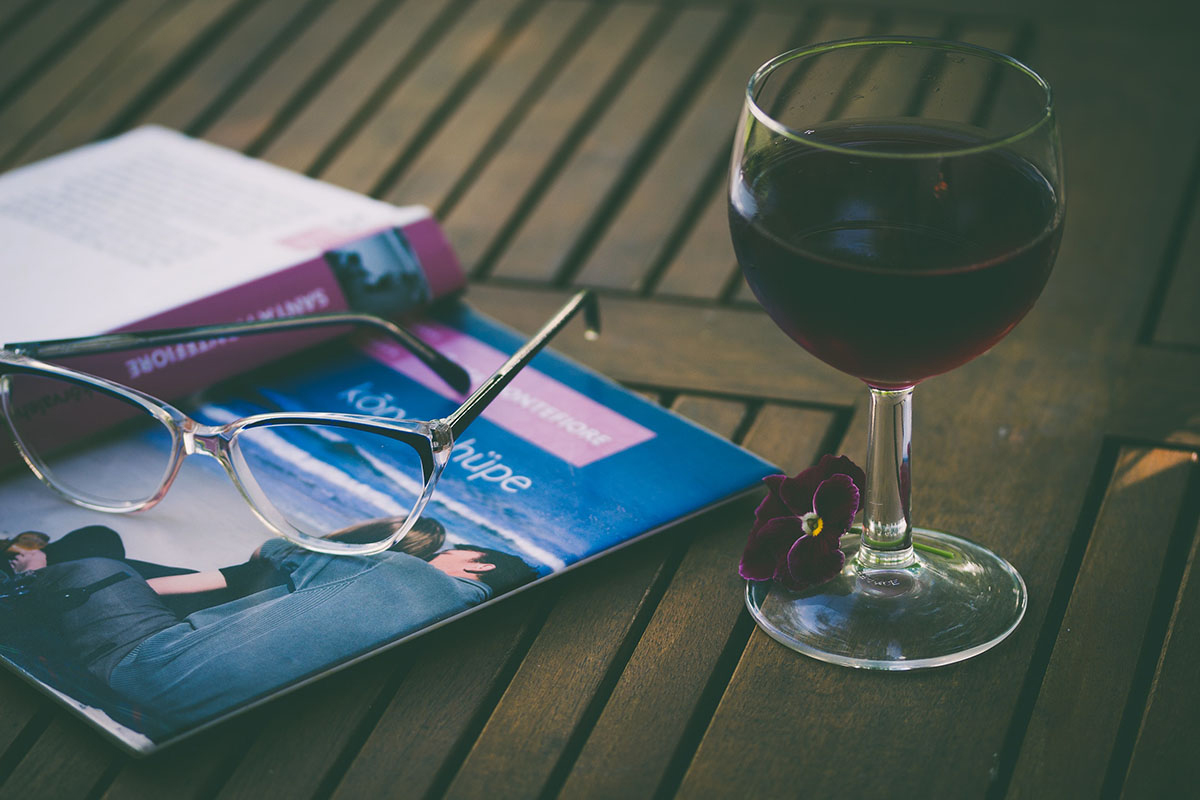 book and glass of wine on table