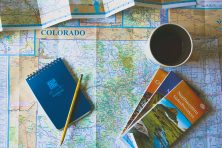 coffee and notepad on top of various colorado maps