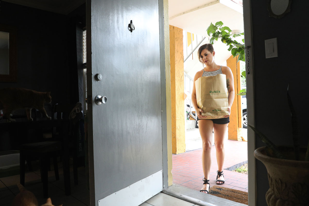 woman walking through door of apartment with groceries in paper bag