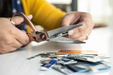 A young woman cuts up multiple credit cards showing credit card debt, consolidation and bankruptcy