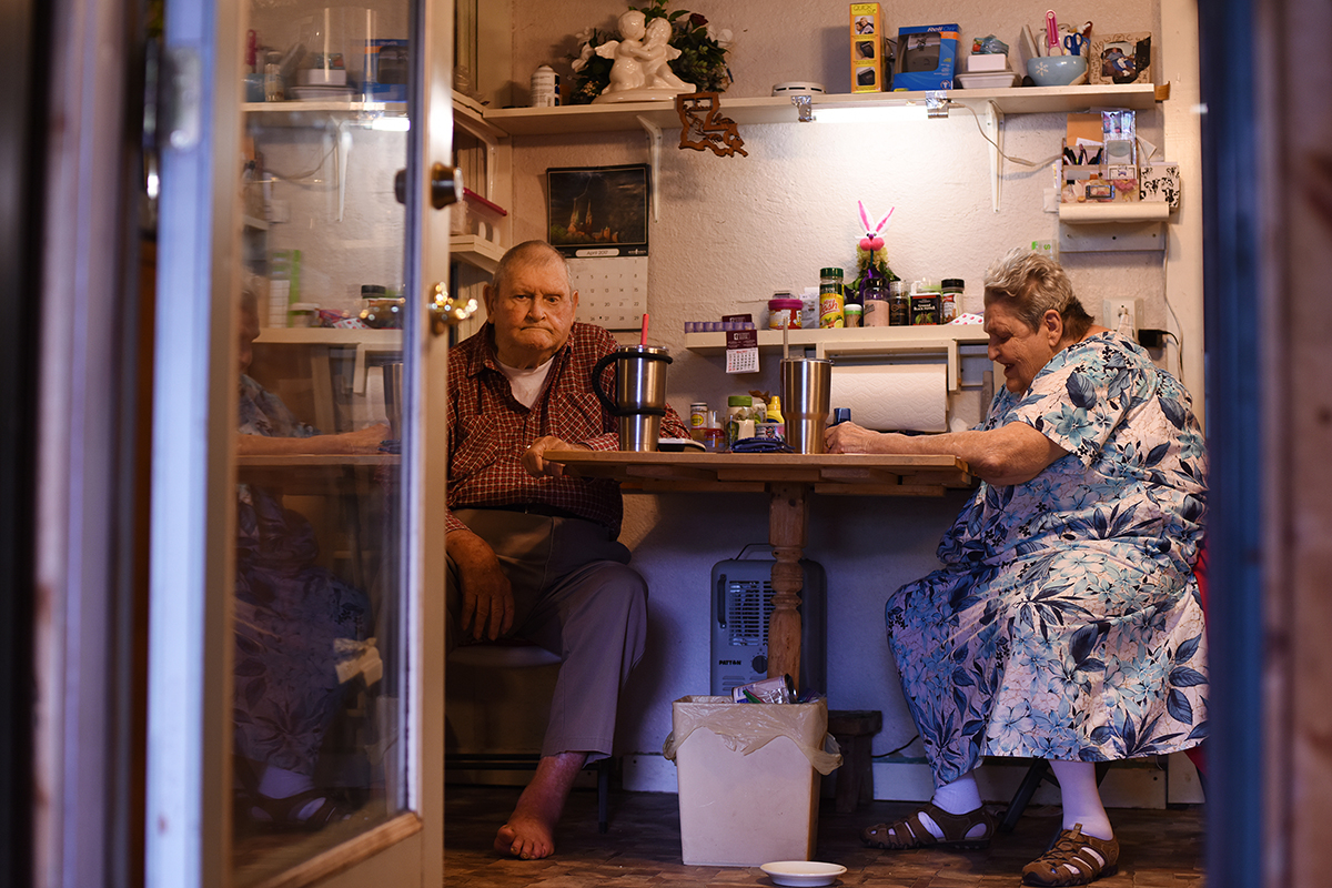 Charlie Russell and Betty Russell sit at their kitchen table as they wait for dinner to be ready to eat at their home in Buncombe, Illinois.