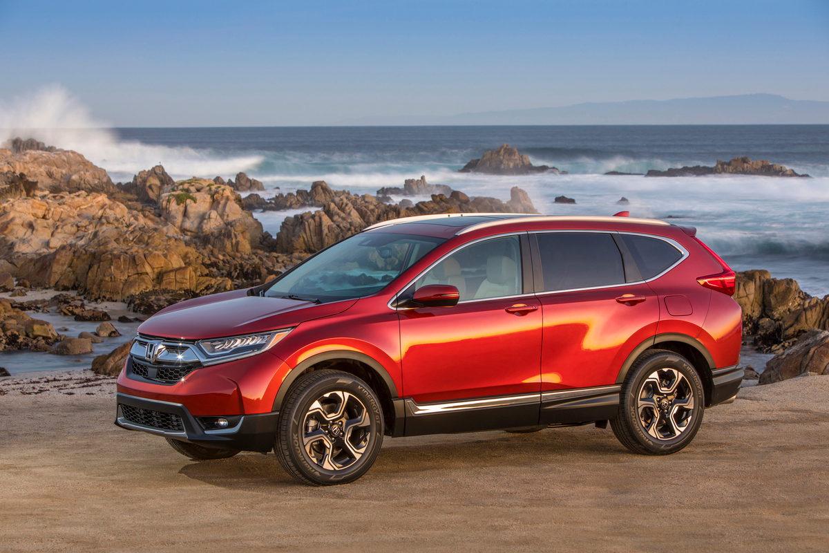 a red 2017 honda CR-V parked with a beach in the background