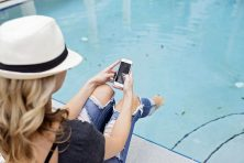 girl poolside on her smartphone