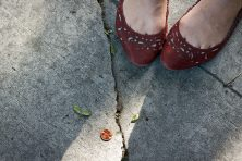 A girl in red shoes finds a penny on the sidewalk.