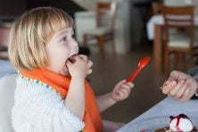 child with orange plastic spoon eating with hand in mouth sharing with woman a piece of chocolate cake with vanilla ice cream at restaurant