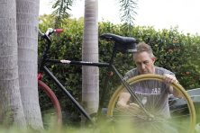 A middle-aged man touches up a bicycle to sell as his side-gig.