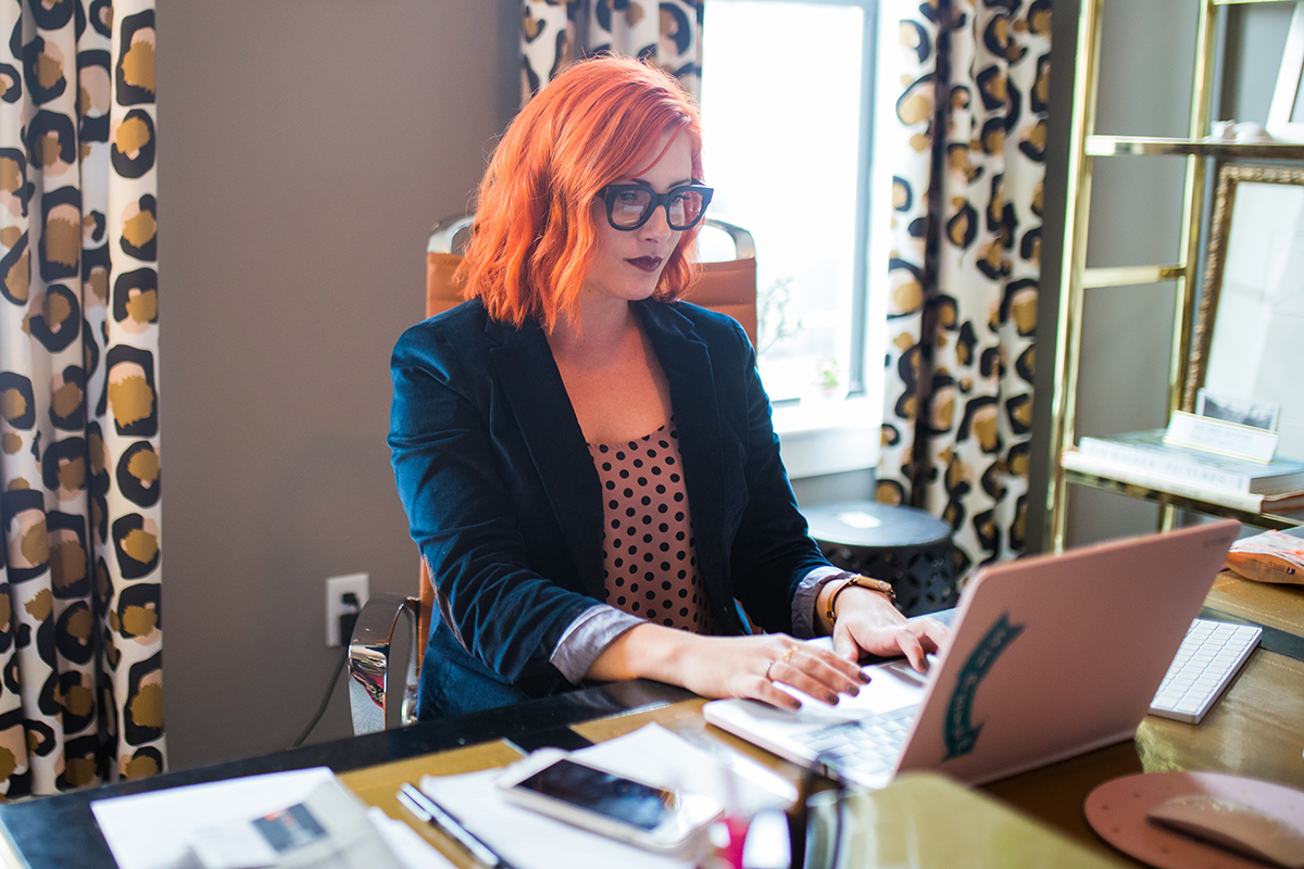 A young woman with bright red hair works from home on her laptop.
