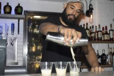 A young bartender makes drinks for customers at a bar in Florida.