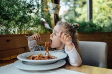 Little preschool girl is having a spaghetti dinner in restaurant