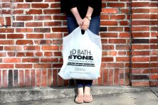 woman leaning against a brick wall with a bed, bath and beyond bag