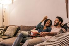 young couple sitting on living room couch watching a movie