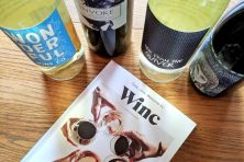 Winc guide next to wine bottles