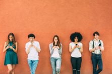 Five people texting holding cell phones while leaning against an orange wall