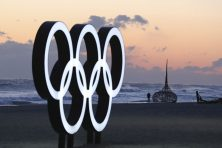 A visitor walks along the beach near the Olympic Rings in Gangneung, South Korea