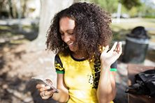 A woman smiles as she looks at her phone in a park in Tampa, Fla.