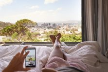 A woman in bed taking a picture of the view from her bedroom.