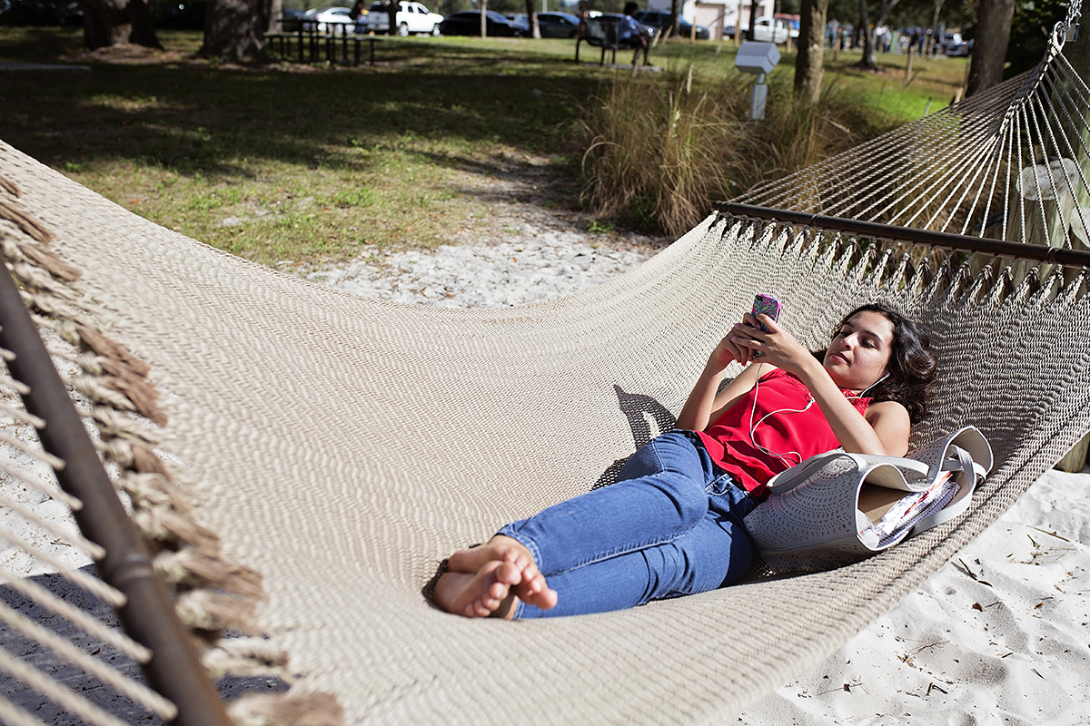 Carla Garcia relaxes on her phone in between classes on the University of South Florida Campus