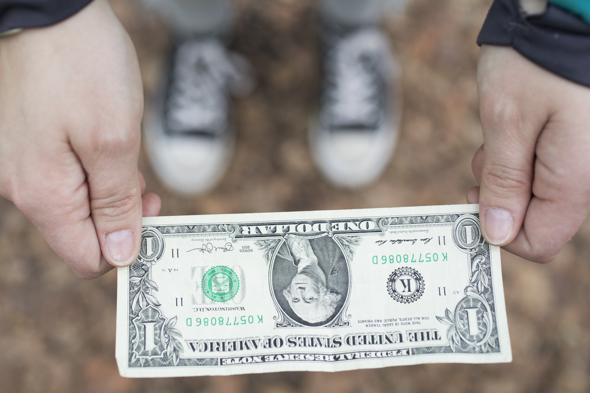 A crisp dollar bill being held out over a pair of blurred out sneakers.
