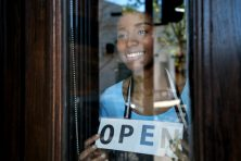 a happy woman is seen through a business window holding an open sign.
