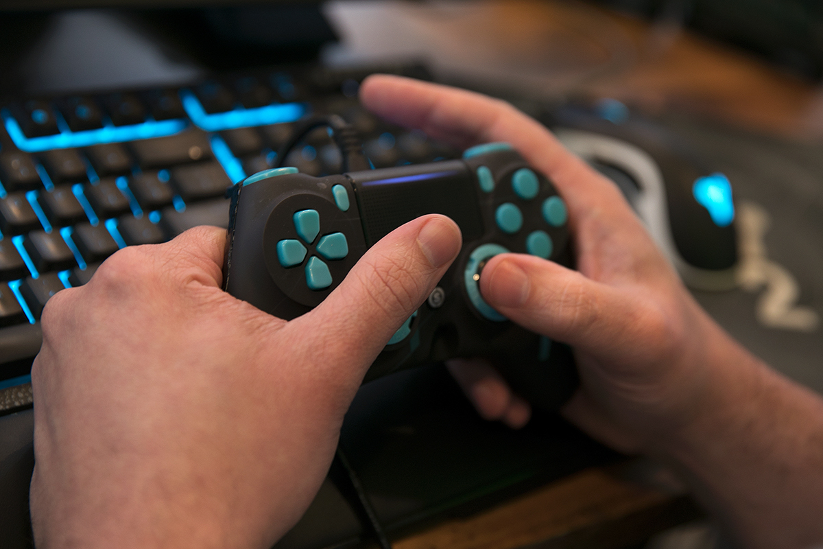 Detail shot of Cory Michael's hands holding a video game controller.