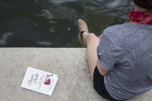 A woman sits on a sea wall while reading a book about debt.