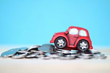 A toy car climbs a hill of money coins
