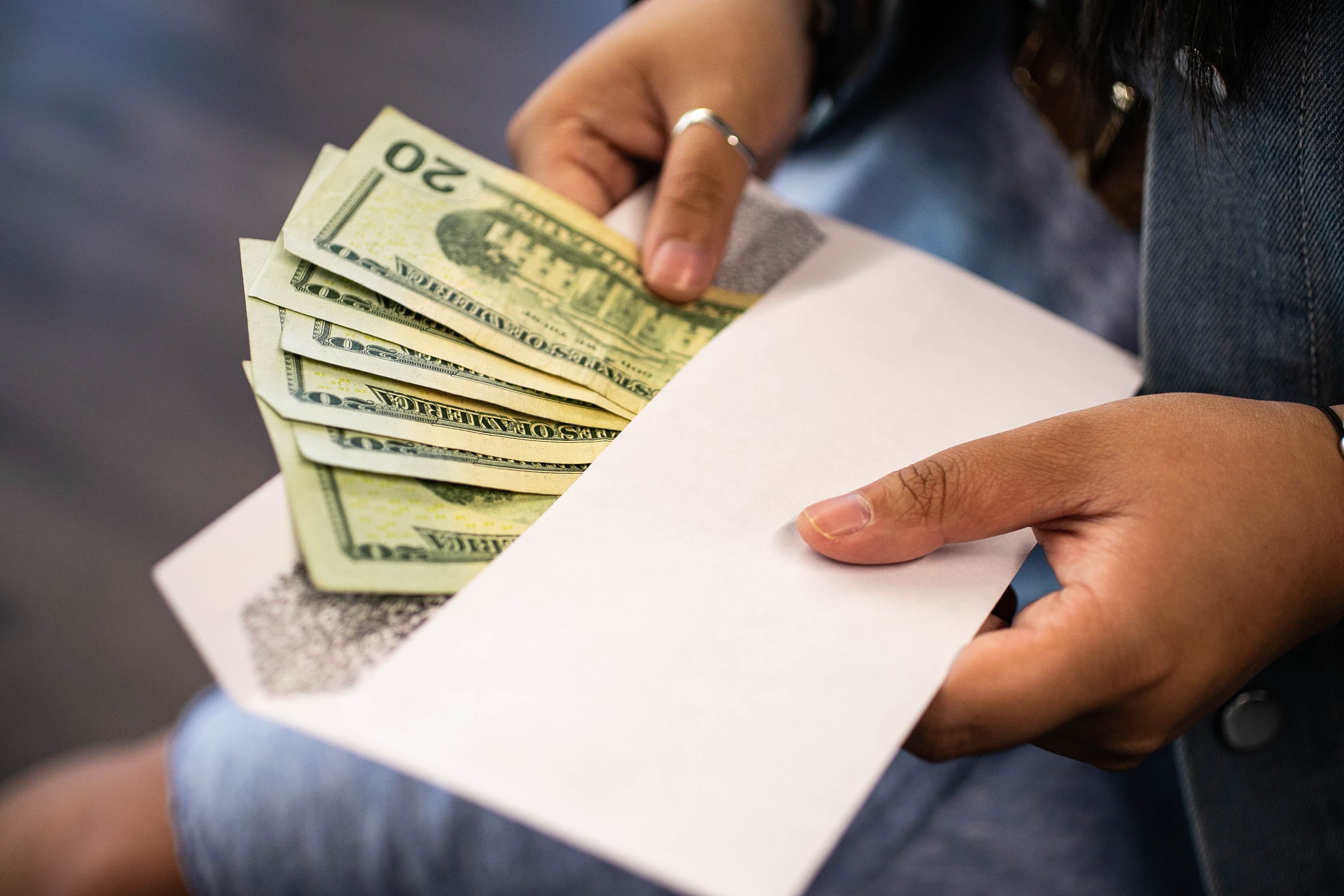A woman's hand puts cash in an envelope.
