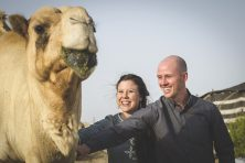 A man and woman pet a camel in the desert