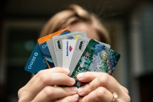 A woman's hands hold a lot of credit cards.