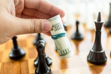 A hand moves a small roll of U.S. dollars on a chess board.