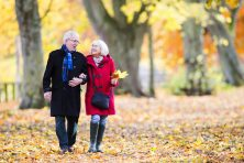 Senior couple are walking together through the autumn woods.