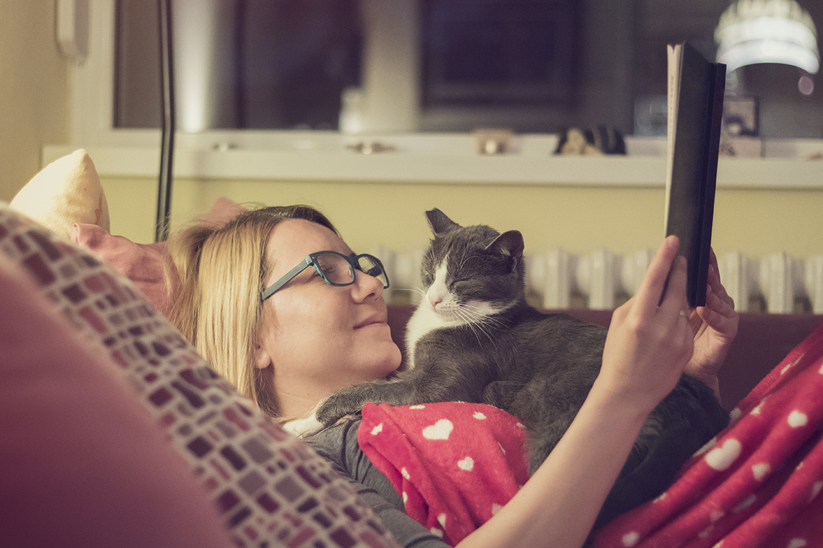 Woman reading with her cat