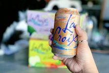 woman holding can of la croix in hand