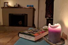 A candle and a book on a sidetable in an apartment with a mantle and a fireplace.