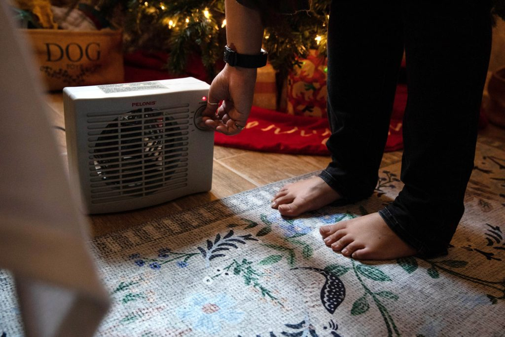 A woman turns on a space heater in her home.