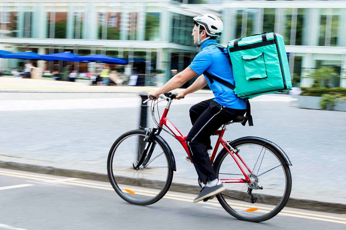 A man rides a bike with a pizza delivery case strapped to his back.